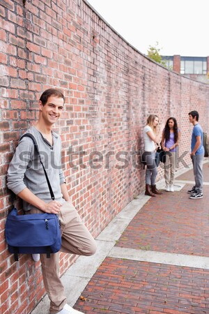Portrait of a male student leaning on a wall outside a building Stock photo © wavebreak_media