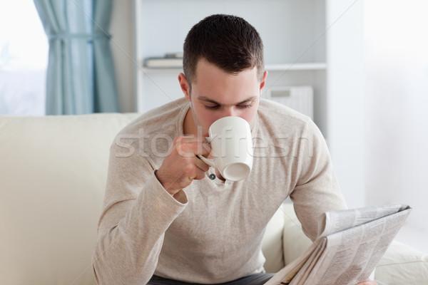 молодым человеком чтение Новости кофе гостиной бумаги Сток-фото © wavebreak_media