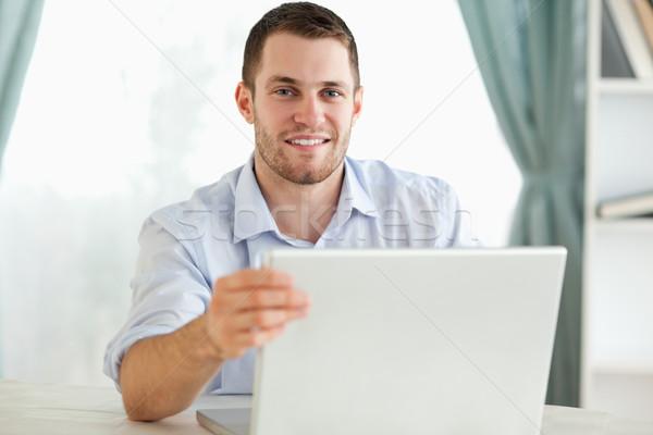 Gülen genç işadamı oturma arkasında tablo Stok fotoğraf © wavebreak_media
