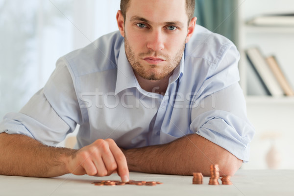 Desperate young businessman counting his small coins Stock photo © wavebreak_media