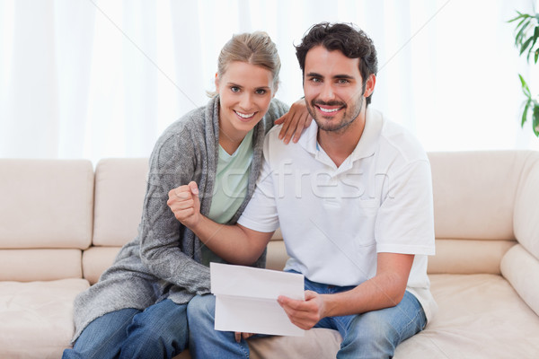 Delighted couple reading a letter in their living room Stock photo © wavebreak_media