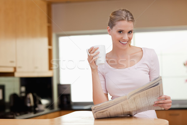 Young woman reading the news while having coffee in her kitchen Stock photo © wavebreak_media