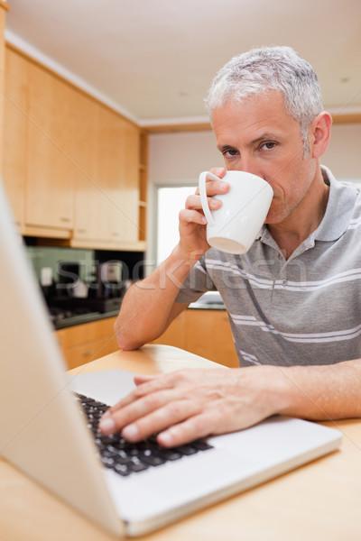 Сток-фото: портрет · человека · используя · ноутбук · питьевой · чай · кухне