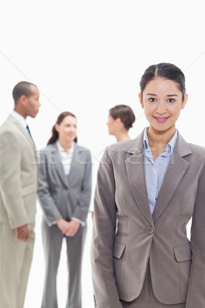 Businesswoman smiling with co-workers talking in the background against white background Stock photo © wavebreak_media