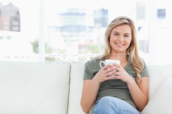 A woman holding up a cup in front of her at shoulder height, with a smile as she sits on the couch. Stock photo © wavebreak_media