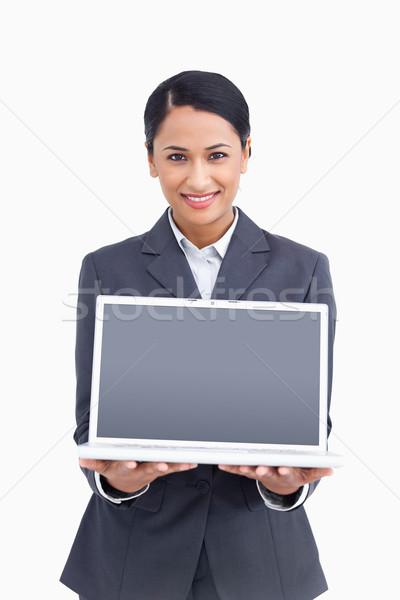Stock photo: Close up of smiling saleswoman presenting screen of laptop against a white background