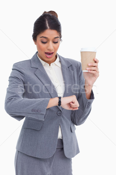 Shocked female entrepreneur with paper cup looking at her watch against a white background Stock photo © wavebreak_media