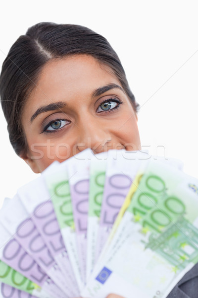 Close up of female entrepreneur hiding her face behind bank notes against a white background Stock photo © wavebreak_media