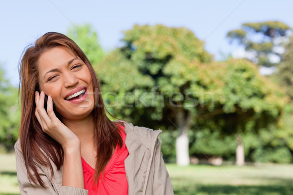 Young woman laughing joyfully while on the phone in a bright grassland  area Stock photo © wavebreak_media