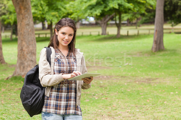 Young student using a tactile tablet in a park Stock photo © wavebreak_media