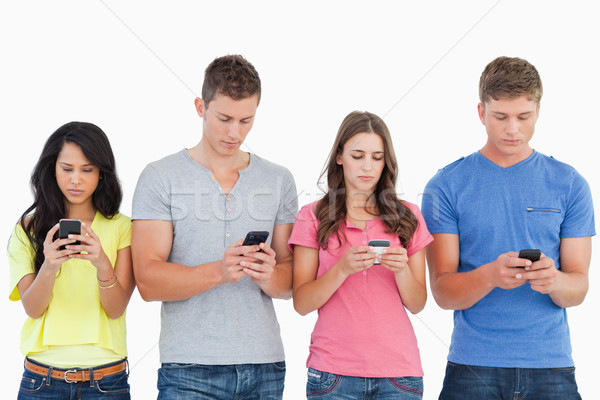 A group of people using their phones and sending texts as they stand beside each other  Stock photo © wavebreak_media