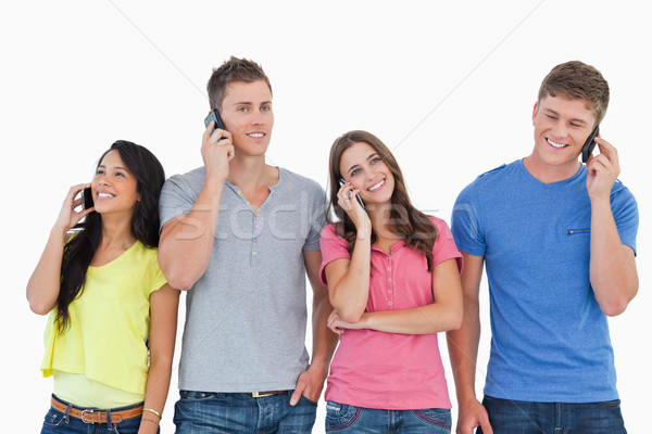 A group of friends on their phones making calls as they smile and stand beside each other  Stock photo © wavebreak_media