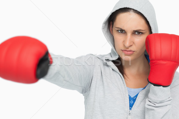 Stern woman in sweatshirt boxing against white background Stock photo © wavebreak_media