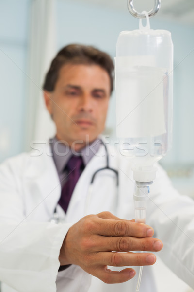 Concentrated doctor connecting the phial in hospital Stock photo © wavebreak_media