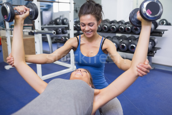 Trainer teaching woman lifting weights in gym Stock photo © wavebreak_media