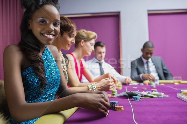 Smiling woman looking up from poker game in casino Stock photo © wavebreak_media