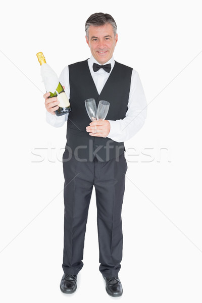 Stock photo: Smiling waiter in suit holding glasses and champagne bottle