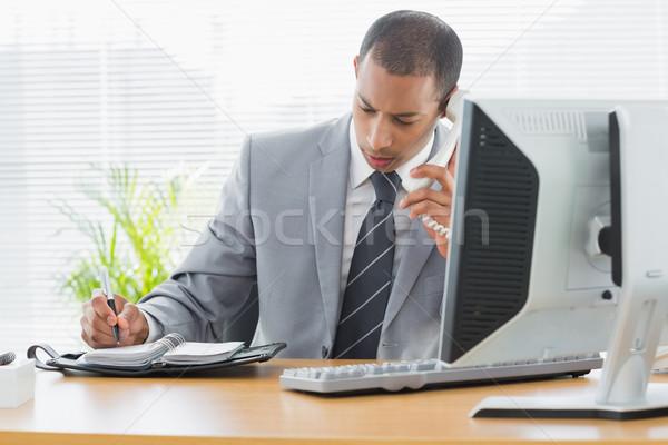 üzletember számítógéphasználat telefon irodai asztal koncentrált fiatal Stock fotó © wavebreak_media