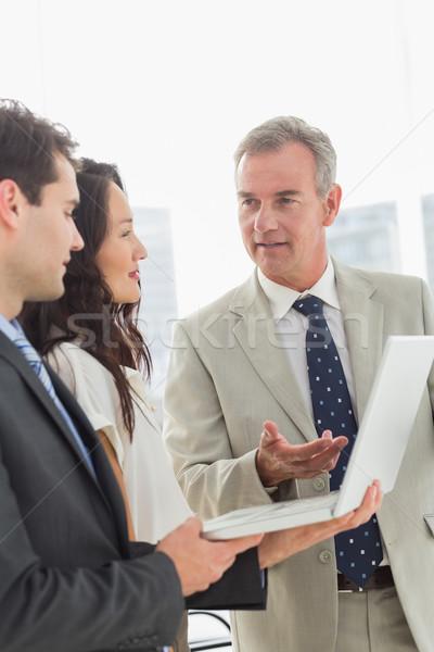 Foto stock: Equipe · de · negócios · em · pé · trabalhando · laptop · juntos · escritório