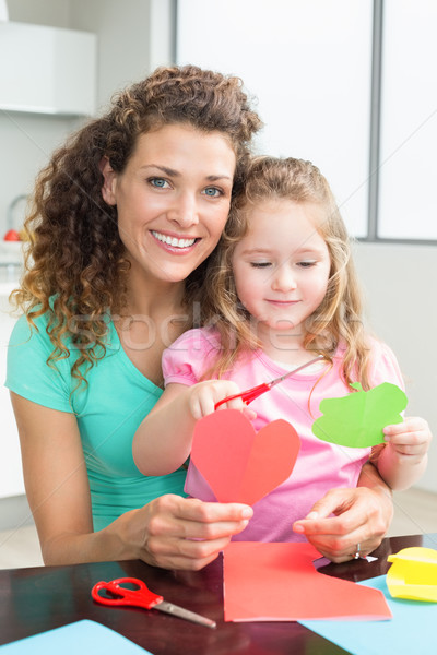 Cute little girl cutting paper shapes with mother at the table Stock photo © wavebreak_media