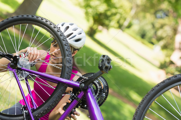 Woman trying to fix chain on mountain bike in park Stock photo © wavebreak_media