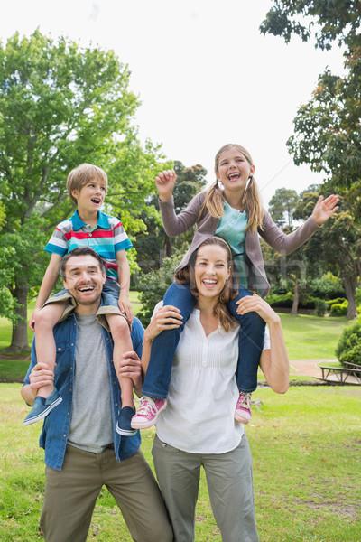 Happy parents carrying kids on shoulders at park Stock photo © wavebreak_media