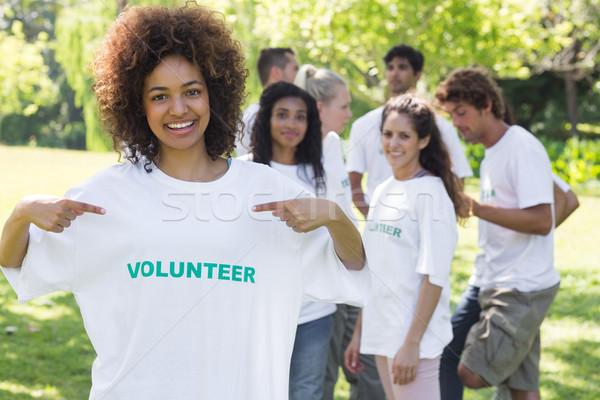 Happy volunteer pointing at tshirt Stock photo © wavebreak_media