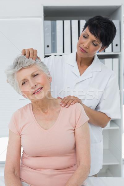 Female chiropractor doing neck adjustment Stock photo © wavebreak_media