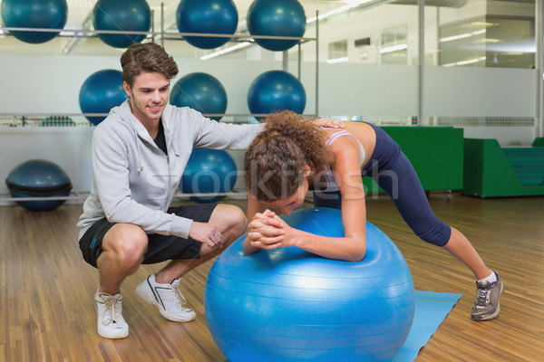 Trainer watching his client using exercise ball Stock photo © wavebreak_media