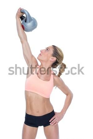 Female blonde crossfitter lifting kettlebell above head Stock photo © wavebreak_media