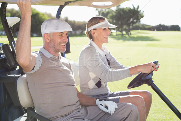 Stock photo: Happy golfing couple smiling in their buggy