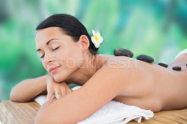 Stock photo: Beautiful brunette enjoying a hot stone massage