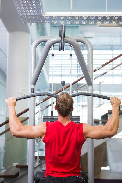Strong man using weights machine for arms Stock photo © wavebreak_media