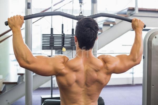 Gespierd man machine gymnasium achteraanzicht Stockfoto © wavebreak_media
