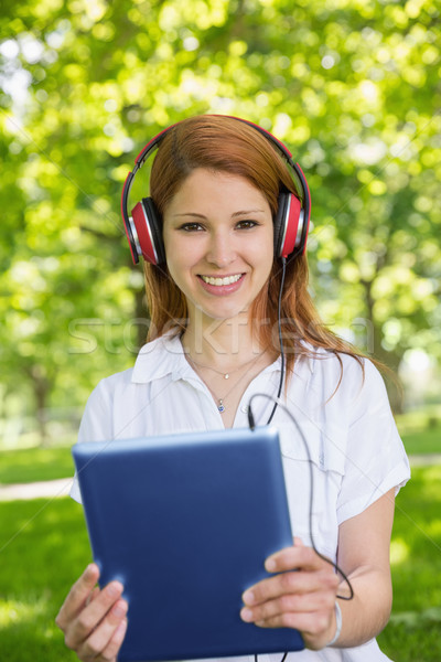 Pretty redhead using her tablet pc while listening to music in t Stock photo © wavebreak_media