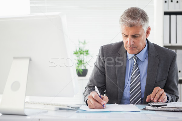Focused businessman writing something down Stock photo © wavebreak_media
