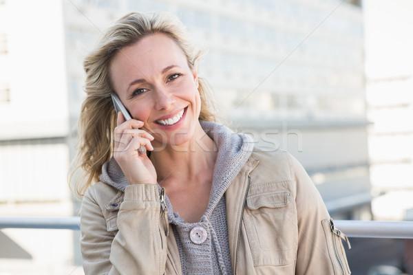 Souriant permanent téléphone ville femme Photo stock © wavebreak_media