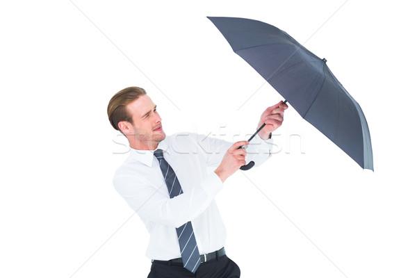 Businessman holding umbrella to protect himself Stock photo © wavebreak_media