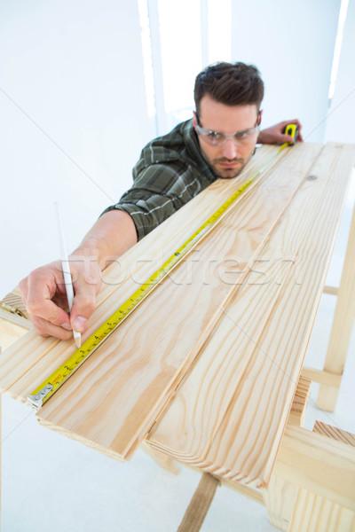 Worker using measure tape to mark on wooden plank Stock photo © wavebreak_media