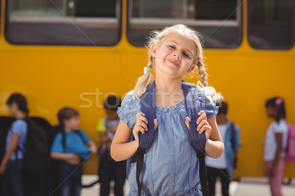 Cute pupils smiling at camera by the school bus Stock photo © wavebreak_media