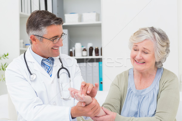 Male doctor examining patients hand at table Stock photo © wavebreak_media