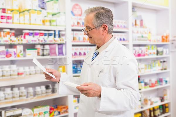 Senior pharmacist looking at medicine and prescription  Stock photo © wavebreak_media
