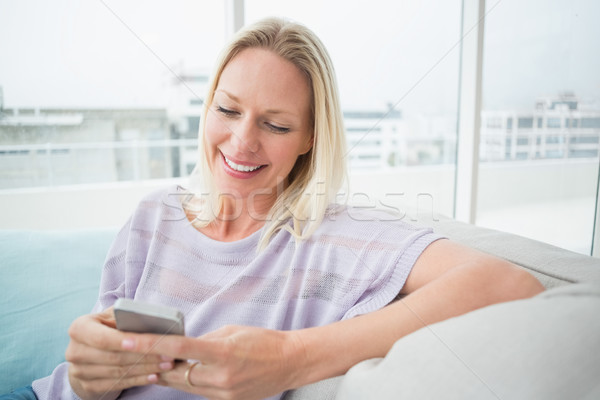 Woman text messaging through mobile phone in living room Stock photo © wavebreak_media