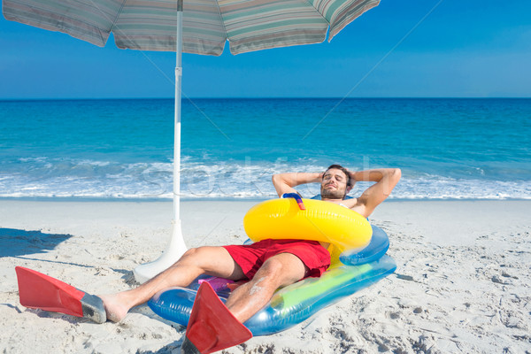 Man lying on the beach with flippers and rubber ring Stock photo © wavebreak_media