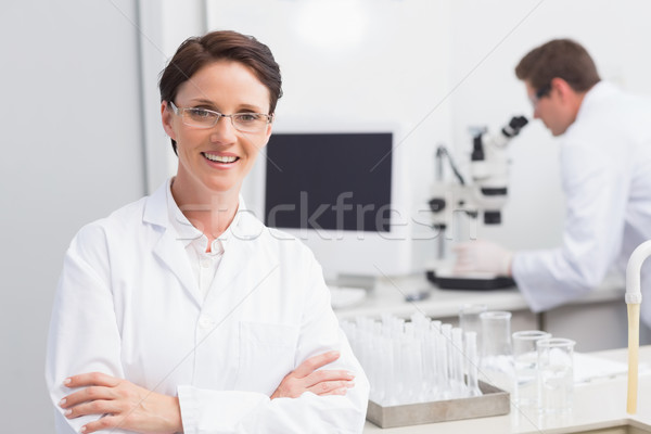 Scientist smiling at camera arms crossed and another working wit Stock photo © wavebreak_media