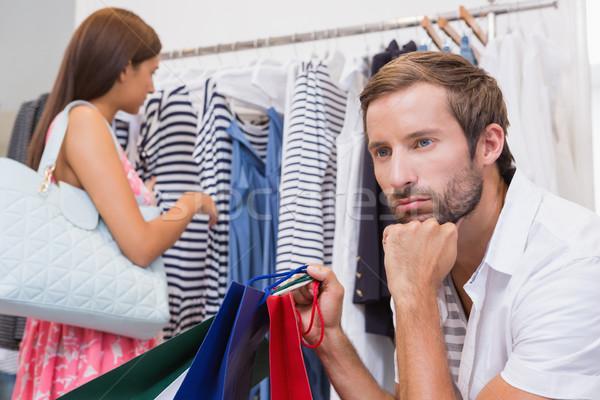 Aburrido hombre sesión espera mujer boutique Foto stock © wavebreak_media