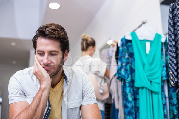 Aburrido hombre sesión compañera ropa tienda Foto stock © wavebreak_media