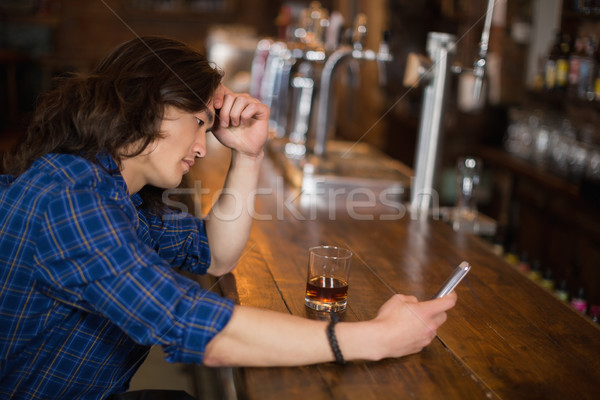 Depressed young man using mobile at pub Stock photo © wavebreak_media