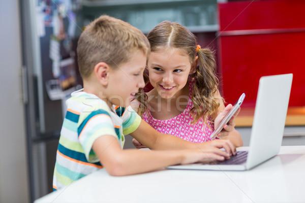 Irmãos usando laptop telefone móvel cozinha casa beber Foto stock © wavebreak_media