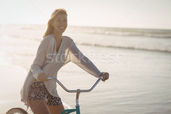 Portrait of smiling woman riding bicycle at beach Stock photo © wavebreak_media